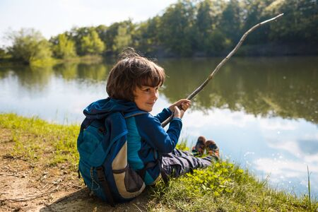 A boy with a backpack sits on the lake with a wooden stick. Little fisherman. A child catches fish in the river. A boy sits on the grass and looks at the water.
