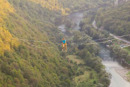 Highline on the background of the mountains and river. A man sits on a stretched sling. Performance of a tightrope walker. Highliner balances over the abyss. The man is trying to get up after a fall. Zdjęcie Seryjne