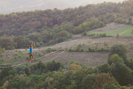 A man is walking along a stretched sling. Highline in the mountains. Man catches balance. Performance of a tightrope walker in nature. Highliner on the background of the mountains.