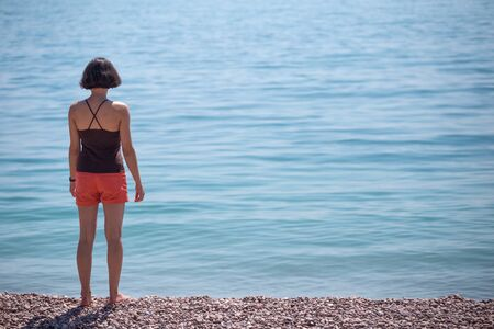 A woman stands on the seashore and looks into the distance. Slender girl looks at the sea. A brunette is standing on the beach.