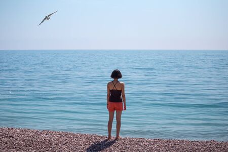 A woman stands on the seashore and looks into the distance. Slender girl looks at the sea. A brunette is standing on the beach. A seagull flies over the water.