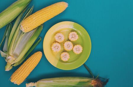 A plate with corn on a turquoise background. Corn slices. Cereal product. A dish of corn. Summer harvest. Corn husk.