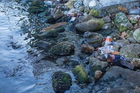 Garbage on the seashore. Plastic bottles float in the water. Garbage washed ashore. Environmental pollution. Ecological catastrophy. Stock Photo
