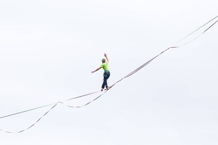 Highline on the background of the cloudy sky. A man is walking along a stretched sling. Performance of a tightrope walker on a background of clouds. Man balances over the abyss. A decisive step.