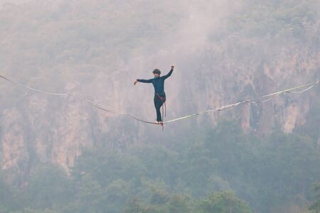 A woman is walking along a stretched sling. Highline in the mountains. Woman catches balance. Performance of a tightrope walker in nature. Highliner in the fog. Stock Photo