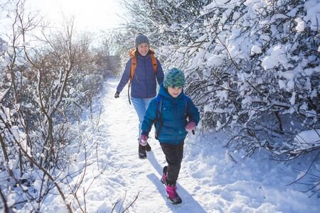 The child runs away from mom. A woman walks with a child in a winter park. The boy spends time with his mother. Mother's love. Walk through the snowy forest. Family walk.