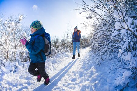 The child runs away from mom. A woman walks with a child in a winter park. The boy spends time with his mother. Mothers love. Walk through the snowy forest. Family walk.