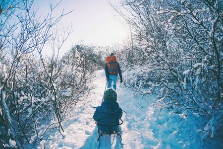 A woman pulls a sled with a child. Mother walks with her son through a snowy forest. Winter walk in the park. The boy rides on a sled. Winter activities with children.