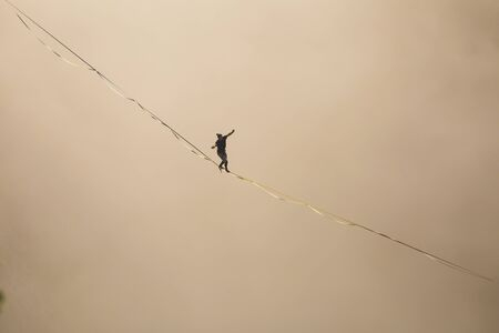 a man walks along a stretched sling high above the clouds. highliner catches the balance on a long and high sling pull in a canyon. Extreme sports in Bosnia and Herzagovina Stock Photo