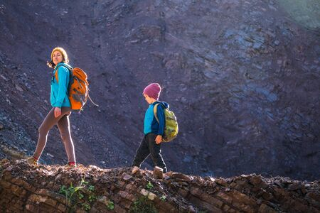 A woman and her child walk along a mountain trail. A boy with a backpack travels with his mother. Hike with children. The kid walks through the forest. Active summer holidays.