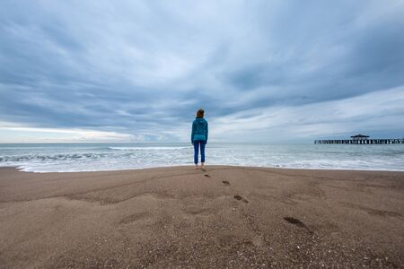 A girl stands on a sandy beach. A woman stands in the water in the cold season. Walk along the ocean coast. Footprints in the sand. The girl in the hat looks at the sea. Beautiful sky with clouds.