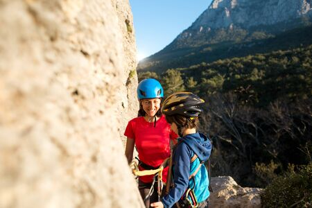 The child in helmet is instructed to go through the climbing route. The trainer teaches the child to use safety equipment. Mountain climbing for children. A woman passes via ferrata with a boy.
