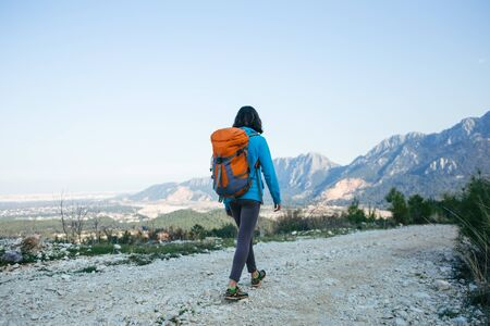 A woman with a backpack is walking along a mountain road. Girl on a background of beautiful mountains. Traveling to scenic spots. Hiking alone.
