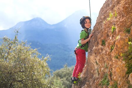 The child is climbing on a natural terrain. A boy climbs a rock on a background of mountains. Extreme hobby. Athletic kid trains to be strong. Rock climbing safety.
