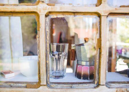 Eine alte zerkratzte Geysir-Kaffeemaschine steht in der Nähe des Fensters. Glas- und Geysir-Kaffeemaschine auf der Fensterbank eines alten Holzhauses.