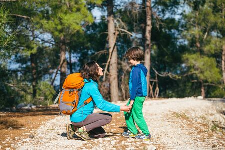 A child hugs mom in the park. A woman with a backpack walks with her son in the forest. Boy travels with his mother. Mom's embrace.