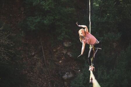 A woman is walking along a stretched sling over a forest, Highliner balances over the abyss, Highline in Turkey, Purposeful girl goes to the goal. Foto de archivo