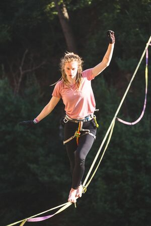A woman is walking along a stretched sling. Highline in the forest. Woman catches balance. Performance of a tightrope walker in nature.