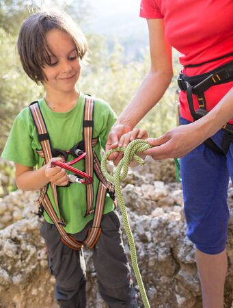 The mother teaches the child to tie a safety knot for climbing, Protective equipment for climbing and sports tourism, A boy learns to knit the safety knot from the rope, Climbing rope for belaying.  Stock Photo