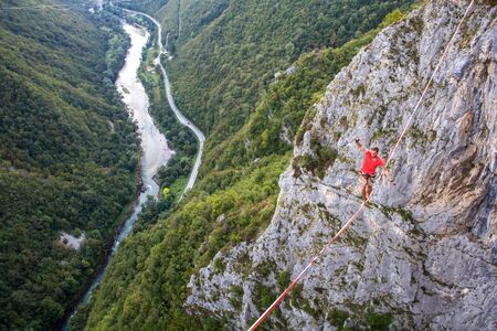 A man is walking along a stretched sling. Highline in the mountains. Man catches balance. Performance of a tightrope walker in nature. Highliner on the background of the mountains and river. Standard-Bild