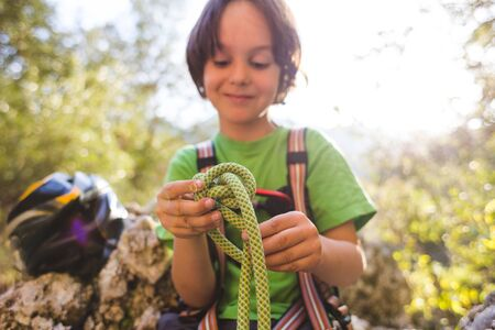 A child learns to knit the safety knot from the rope. Climbing rope for belaying. A little boy is trying to tie a knot. Scout training. Children's hands and safety rope. Teaching children. Stock Photo
