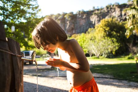 Tired of the heat, the child washes his body with water from a tap in the courtyard of the house. The boy is doused with tap water. Hot Summer. Spray. Vacation in the village.