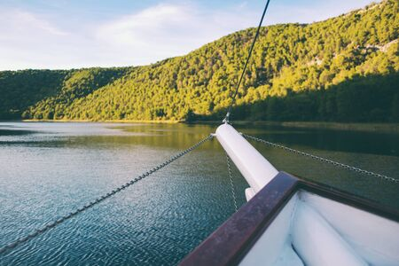 The front of the yacht floating on the river in the national park of Croatia, River transport, Motor boat excursion.