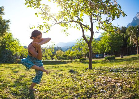 The girl practices yoga on the green grass on a background of green trees and mountains, A woman performs asanas at sunset, Meditation in nature, Exercise for the development of balance.