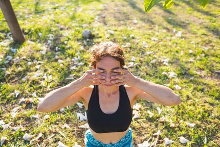 Woman does self-massage of the face, The girl practices yoga on the green grass on a background of green trees, A woman performs asanas at sunset, Meditation in nature, Female fingers on the face.