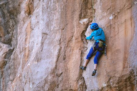 A woman in a helmet climbs a beautiful orange rock. Climbing protective equipment. Safety in climbing. Rock climber overcomes a difficult route on a natural terrain. Rock climbing in Turkey.