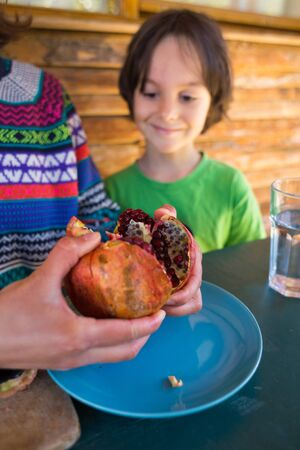 Ripe juicy pomegranate on a blue plate. A child eats pomegranate seeds. Healthy fruit divided into two halves.