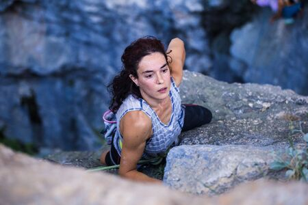 A woman is climbing in Turkey, Turkish woman climbs the rock, Extreme hobby, Overcoming a difficult climbing route, Overcoming the fear of heights, Climbing effort. Banque d'images