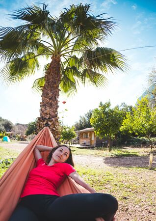 A smiling woman is lying in a hammock. The girl is resting in nature. Camping. Holidays in Turkey. The brunette lies in a hammock on a background of palm trees.
