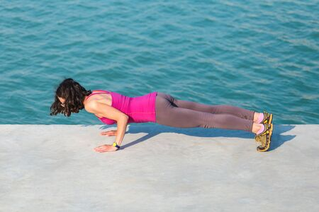 Woman warming up before jogging. The girl is stretched on the city promenade. Training in the city. Brunette doing sports exercises on a background of water. Stretching. Workout.