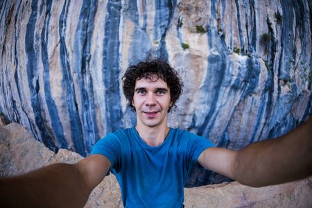 A man takes a selfie against a background of beautiful blue rocks, A man travels to picturesque places of the world, Rocks of Turkey, Rock climbing in Turkey. 版權商用圖片