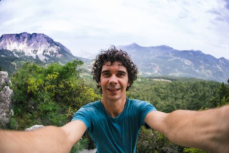 A man takes a selfie against the backdrop of a beautiful mountain valley and rocks, A man travels through the picturesque places of the world, Turkey Rocks, Rock Climbing in Turkey.