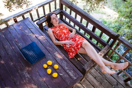 A girl in a red dress lies on the veranda of a wooden house, Woman relaxing from work on the terrace of a summer house, Laptop and lemons on the table.