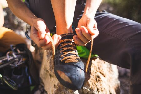 Rock climber puts on climbing shoes and ties shoelaces. A girl sits on a stone and puts on climbing shoes. Preparing to overcome the route. Female hands close-up.