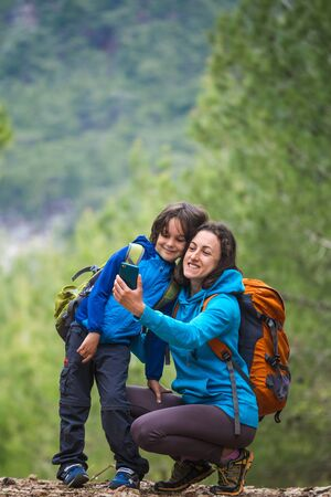 A child with a backpack takes a selfie on a smartphone with mom on the background of a mountain forest, A boy travels with mother, A woman is photographed with her son, Hiking with children.