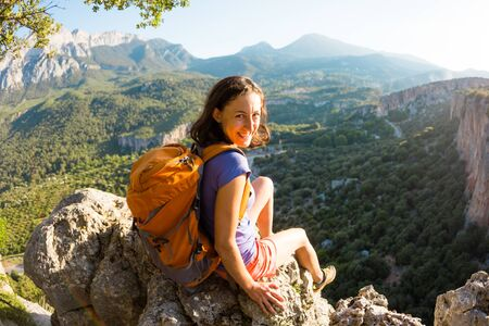 A woman with a backpack sits on top of a mountain and admires the beauty of a mountain valley, The girl travels to beautiful places of Turkey, Reaching the goal, Beautiful landscape.