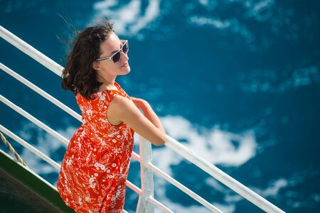 A woman is sailing on a cruise ship, a girl is standing near the fence on a ship and looking at the sea, traveling by ferry, a brunette in a summer dress admires the ocean.