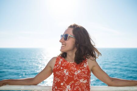 Portrait of a woman on the background of the ocean, a woman is swimming on a cruise ship, a girl is standing near the fence on a ship, traveling by ferry, a brunette in a summer dress admires the sea. Stok Fotoğraf