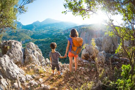 The boy and his mother are standing on the top of the mountain, A woman is traveling with child, Boy with his mother looking at the mountains, Travel with backpacks, Hike and climb with kids.