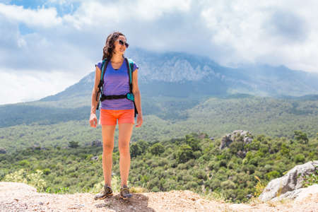 A woman with a backpack stands on top of a mountain and admires the beauty of a mountain valley, The girl travels to beautiful places, Reaching the goal. Beautiful landscape.