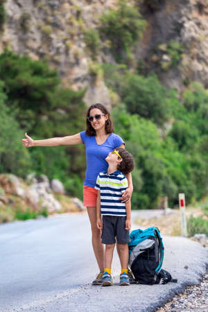 A woman with a child stands on the promenade and looks at the sea, a boy with his mother on a walk along the sea, rest and travel with children, vacation in Turkey.