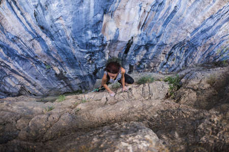 A woman is climbing in Turkey, Turkish woman climbs the rock, Extreme hobby, Overcoming a difficult climbing route, Overcoming the fear of heights, Climbing effort, Emotional girl. Banque d'images