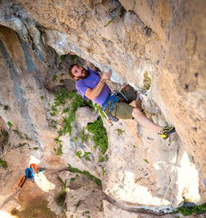 A strong man climbs a cliff, Climber overcomes a difficult climbing route on a natural terrain, Rock climbing in Turkey, Beautiful orange rock. Reklamní fotografie