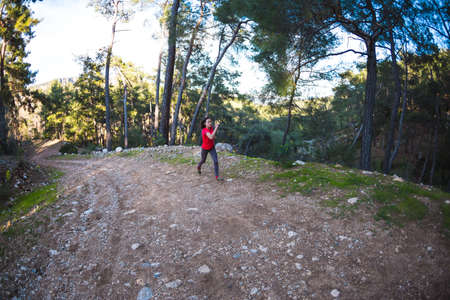 A woman runs along a mountain trail. Runner is training in the forest. Girl jogging in the park. Skyrunning. Fisheye lens.
