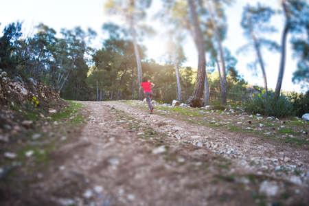A woman runs along a mountain trail. Runner is training in the forest. Girl jogging in the park. Skyrunning. Fisheye lens. Tilt-shift effect.