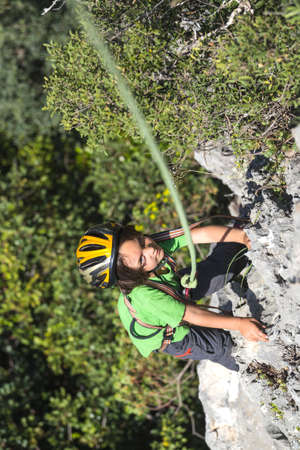 The child is climbing on a natural terrain. A boy in helmet climbs a rock on a background of mountains. Extreme hobby. Athletic kid trains to be strong. Rock climbing safety. Banque d'images